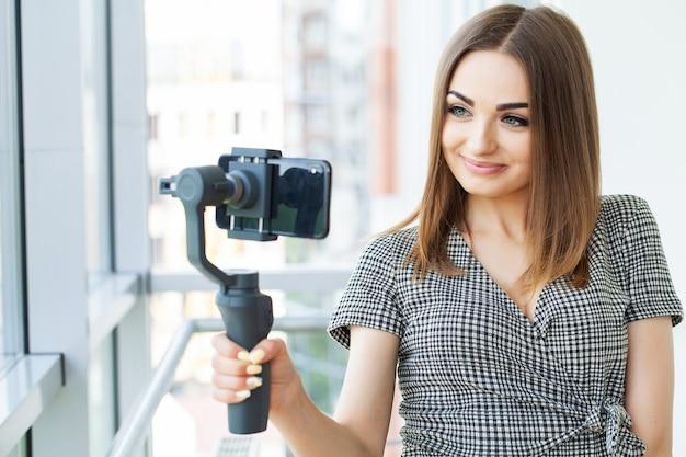Kobieta młody biznes nagrywa blog wideo na smartfonie w biurze firmy.