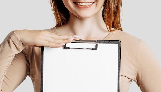 Kobieta młody biznes posiada schowek z pustą przestrzenią na białym tle na szarym tle.