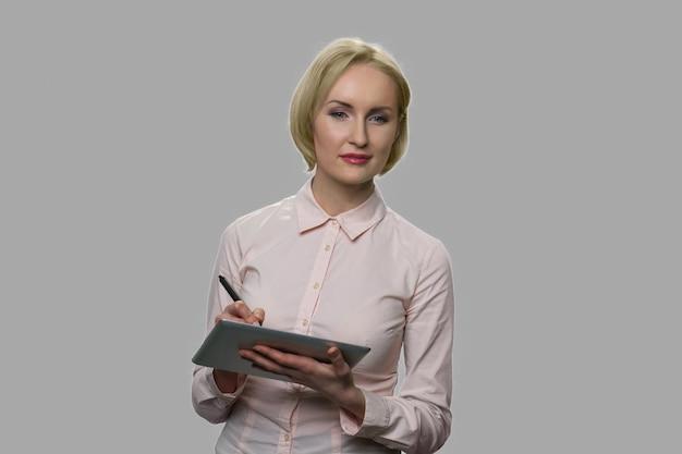 Kobieta młody biznes pracuje na cyfrowym tablecie. kobieta projektant rysunek na komputerze typu tablet na szarym tle.