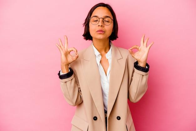 Kobieta młody biznes rasy mieszanej na białym tle na różowej ścianie relaksuje po ciężkim dniu pracy, wykonuje jogę.