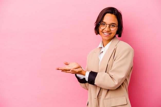 Kobieta młody biznes rasy mieszanej na białym tle na różowym tle, trzymając miejsce na kopię na dłoni.