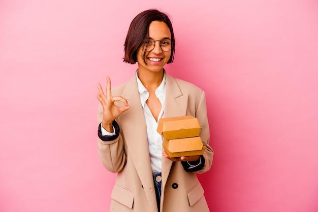 Kobieta młody biznes rasy mieszanej na białym tle na różowym tle wesoły i pewny siebie, pokazując ok gest.