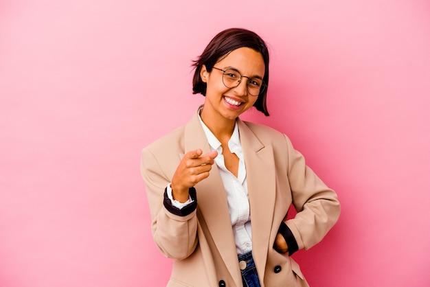 Kobieta młody biznes rasy mieszanej na białym tle na różowym tle wesoły uśmiech wskazujący na przód.