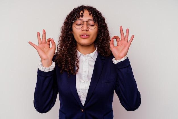 Kobieta młody biznes rasy mieszanej na białym tle relaksuje po ciężkim dniu pracy, wykonuje jogę.