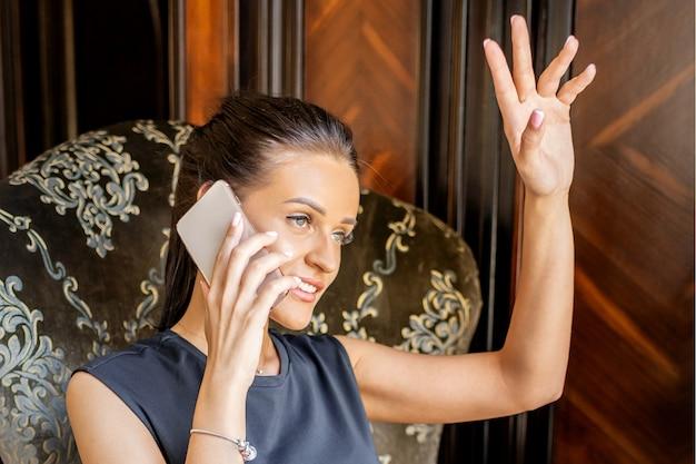 Kobieta młody biznes rozmawia przez smartfona siedząc w fotelu w domu lub w biurze
