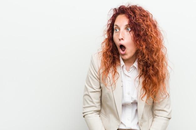 Kobieta młody biznes rudy naturalny na białym tle jest w szoku z powodu czegoś, co widziała.