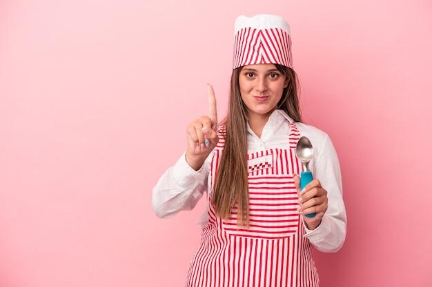 Kobieta młody ekspres do lodów gospodarstwa łyżka na białym tle na różowym tle wyświetlono numer jeden palcem.