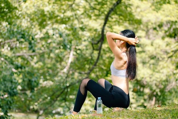 Kobieta młody fitness rozciąganie ciała pod drzewem. koncepcja zdrowej