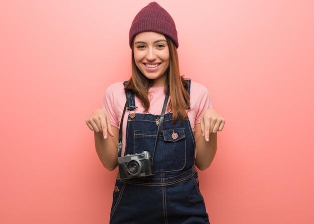 Kobieta młody fotograf ładny, wskazując palcami w dół