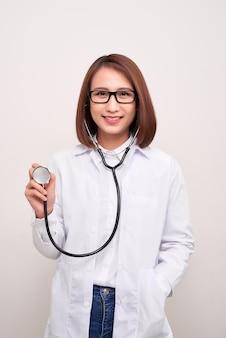 Kobieta młody lekarz posiadający stetoskop na białym tle