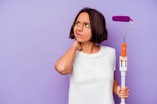 Kobieta młody malarz rasy mieszanej trzymając kij farby na fioletowej ścianie dotykając tyłu głowy, myśląc i dokonując wyboru.
