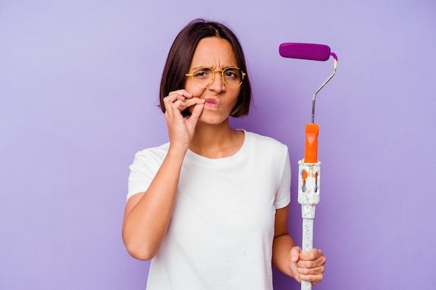 Kobieta młody malarz rasy mieszanej trzymając kij farby na fioletowej ścianie z palcami na ustach, zachowując tajemnicę.