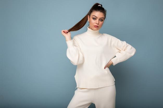 Kobieta młody piękny moda europejska sobie biały sweter na białym tle na niebieskim tle