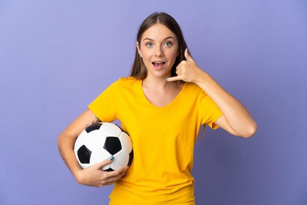 Kobieta młody piłkarz litewski na białym tle na fioletowym tle co telefon gest. oddzwoń do mnie znak