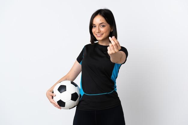 Kobieta młody piłkarz na białym tle na białej ścianie robi pieniądze gestowi