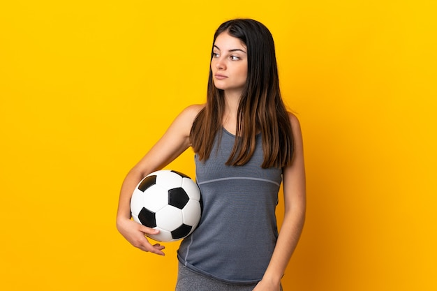 Kobieta młody piłkarz na białym tle na żółtej ścianie, patrząc z boku