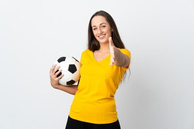 Kobieta młody piłkarz na pojedyncze białe tło, ściskając ręce za zamknięcie dobrą ofertę