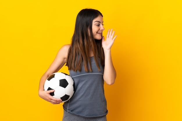 Kobieta młody piłkarz odizolowane na żółto krzycząc z szeroko otwartymi ustami na bok