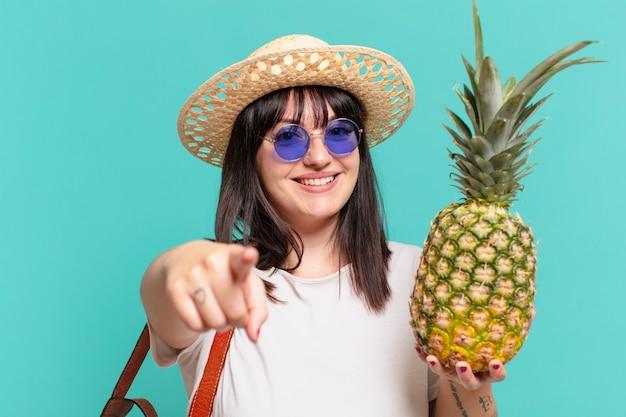 Kobieta młody podróżnik, wskazując lub pokazując i trzymając ananasa