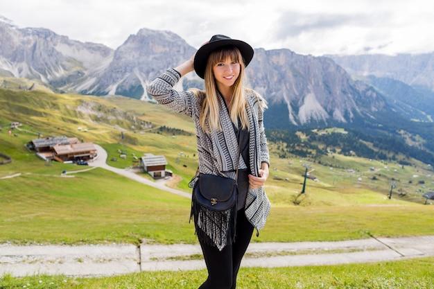 Kobieta młody podróżnik z kapeluszem i plecakiem, podziwiając niesamowity widok na góry