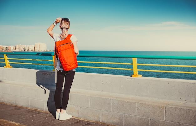 Kobieta młody podróżnik z plecakiem stojąc na molo i patrząc na morze