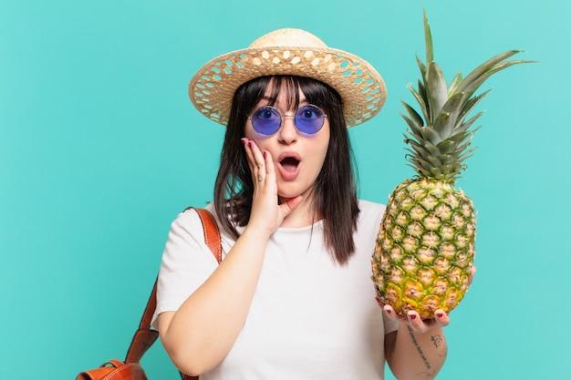 Kobieta młody podróżnik zaskoczony wypowiedzi i trzyma ananas