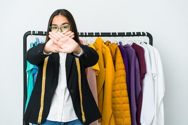 Kobieta młody projektant azjatyckich samodzielnie na białym tle robi gest odmowy