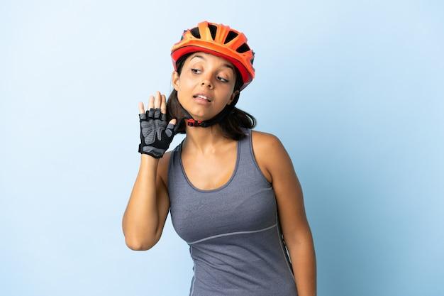 Kobieta młody rowerzysta na białym tle na niebieskim tle, słuchając czegoś, kładąc rękę na uchu