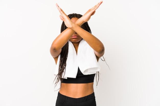 Kobieta młody sport african american na białym tle trzymając dwie skrzyżowane ręce, koncepcja odmowy.