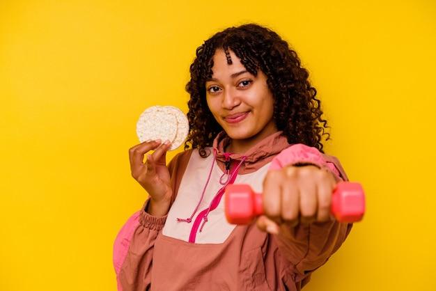 Kobieta młody sport mieszanej rasy jedzenie ciastka ryżowe na białym tle na żółtym tle