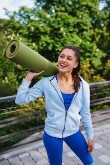 Kobieta młody sport wesoły spaceru w parku miejskim trzymając dywanik fitness.