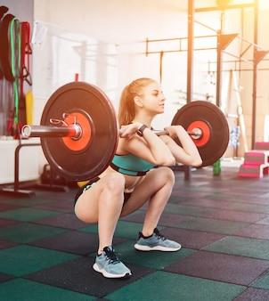 Kobieta młody sportowiec w odzieży sportowej robi przysiady ze sztangą na klatce piersiowej na siłowni