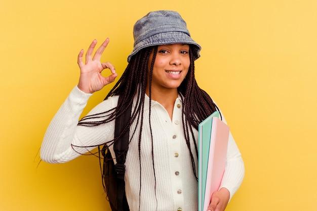 Kobieta młody student african american na białym tle na żółtej ścianie, wesoły i pewny siebie, pokazując ok gest.