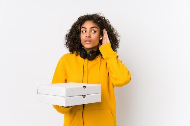 Kobieta młody student african american trzymając pizze, próbując słuchać plotek.