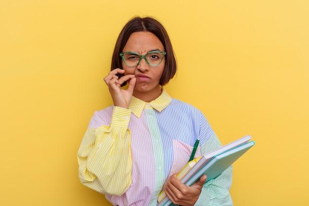 Kobieta młody student rasy mieszanej na białym tle na żółtej ścianie z palcami na ustach, utrzymując tajemnicę.