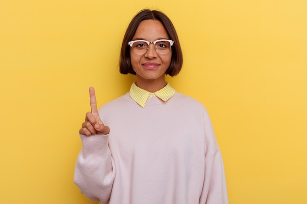 Kobieta młody student rasy mieszanej na białym tle na żółtym tle pokazuje numer jeden z palcem.