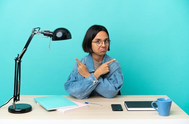 Kobieta młody student rasy mieszanej studiuje na stole, wskazując na boczne, które mają wątpliwości
