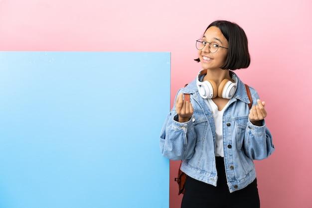 Kobieta młody student rasy mieszanej z dużym sztandarem na białym tle dokonywania gest pieniędzy