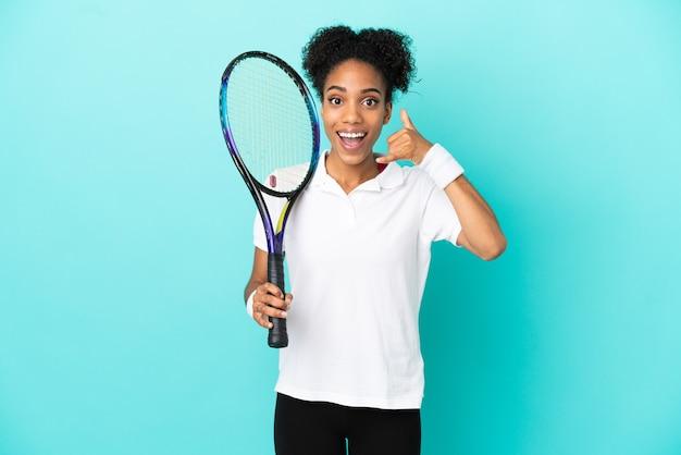 Kobieta młody tenisista na białym tle na niebieskim tle co telefon gest. oddzwoń do mnie znak