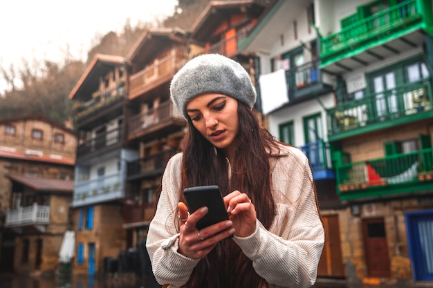 Kobieta młody turysta kaukaski za pomocą smartfona na starym mieście.