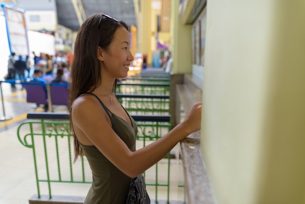 Kobieta młody turysta kupuje bilet podróżny na dworcu
