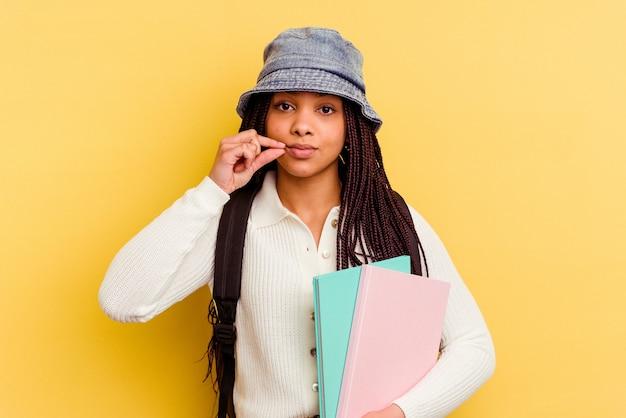 Kobieta młody uczeń afroamerykanów na białym tle na żółtym tle z palcami na ustach z zachowaniem tajemnicy.