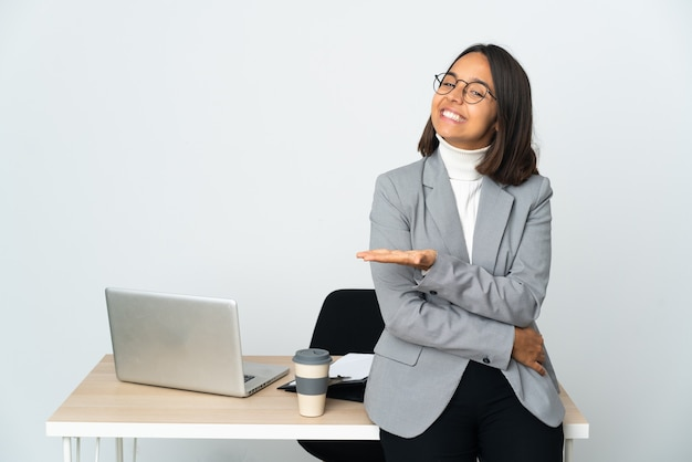 Kobieta młodych biznesowych łacińskiej pracująca w biurze na białym tle prezentując pomysł, patrząc w kierunku uśmiechnięty