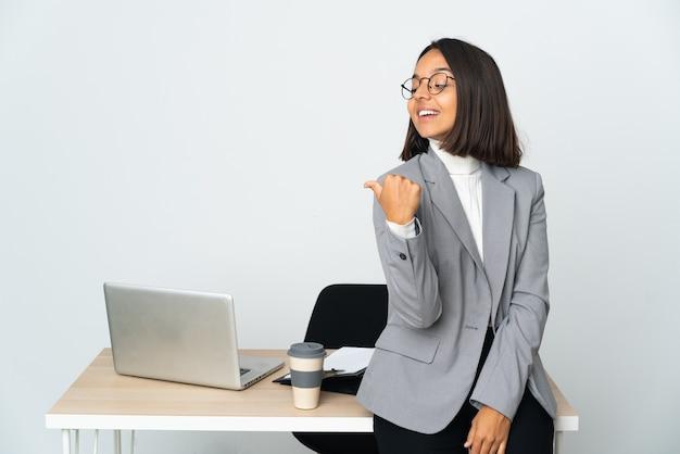 Kobieta młodych biznesowych łacińskiej pracująca w biurze na białym tle, wskazując na bok do przedstawienia produktu