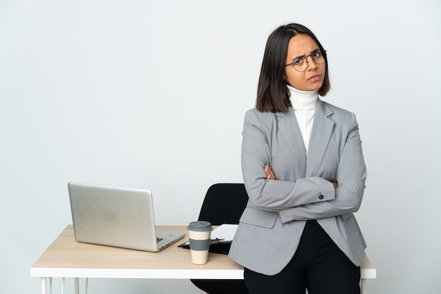 Kobieta młodych biznesowych łacińskiej, pracująca w biurze na białym z nieszczęśliwym wyrazem