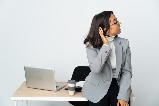 Kobieta młodych biznesowych łacińskiej pracuje w biurze na białym tle, słuchając czegoś, kładąc rękę na uchu