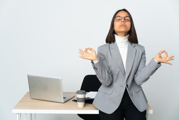 Kobieta młodych biznesowych łacińskiej pracuje w biurze na białym tle w pozie zen