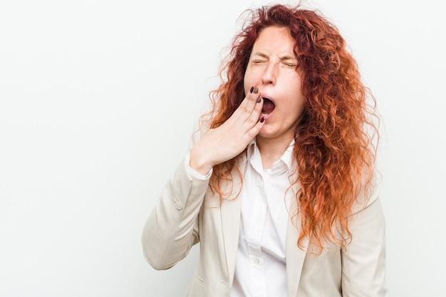 Kobieta młodych biznesowych naturalnych rudowłosy samodzielnie białym tle ziewanie przedstawiający gest zmęczenia obejmujący usta ręką.