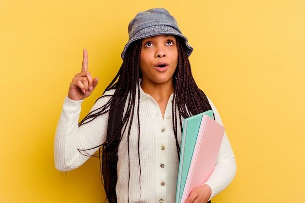 Kobieta młodych studentów afroamerykanów na białym tle na żółtej ścianie wskazując do góry z otwartymi ustami.