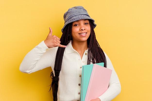 Kobieta młodych studentów afroamerykanów na żółtym tle przedstawiający gest rozmowy telefonicznej palcami.